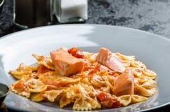 Farfalle用西红柿酱和烤三文鱼 免版税库存图片