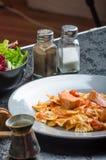 Farfalle用西红柿酱和烤三文鱼 库存照片