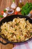 Farfalle макаронных изделий с зажаренными мясом, грибами и овощами стоковое фото