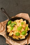 Farfalle. Close up of  Flavorful delicious   traditional italian meal pasta   farfalle with parmesan cheese   fresh basil and black pepper  in cast-iron pan Royalty Free Stock Photo