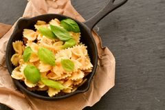 Farfalle. Close up of  Flavorful delicious   traditional italian meal pasta   farfalle with parmesan cheese   fresh basil and black pepper  in cast-iron pan Royalty Free Stock Image