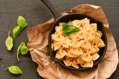 Farfalle. Close up of  Flavorful delicious   traditional italian meal pasta   farfalle with parmesan cheese   fresh basil and black pepper  in cast-iron pan Royalty Free Stock Photography