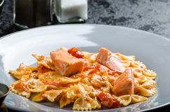 Farfalle com molho de tomate e os salmões roasted Imagens de Stock Royalty Free