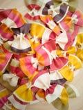 Farfalle de las pastas, modelo italiano de las pastas en una placa de madera Diversos colores de las pastas del farfalle de la co fotografía de archivo libre de regalías