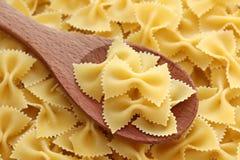 Farfalle della pasta su un cucchiaio di legno Immagini Stock