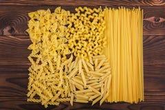 Farfalle, fettuccine, νουντλς, fusilli και penne rigate Διαφορετικά είδη ζυμαρικών σε ένα ξύλινο υπόβαθρο Νόστιμη ιταλική κουζίνα Στοκ Φωτογραφίες