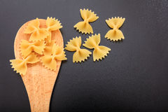 Farfalle in a ladle, black background. Farfalle pasta in a wooden ladle, black background Royalty Free Stock Photography