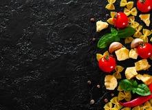 Farfalle makaron, czerwonego chili pieprze, czereśniowy pomidor, basil, czarny pieprz, czosnek, parmesan ser na ciemnym tle Zdjęcie Royalty Free
