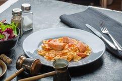 Farfalle mit Tomatensauce und gebratenen Lachsen Stockbild