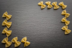 Farfalle noodles at slate black board with copy space. From top view Stock Image