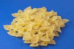 Farfalle Pasta. White farfalle pasta on a blue background Stock Photo