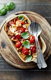 Farfalle pasta baked with chicken fillet and cherry tomatoes Stock Images