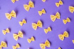 Farfalle pasta bows on a violet background. Royalty Free Stock Photo