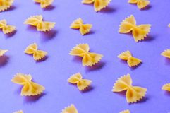 Farfalle pasta bows on a violet background. Royalty Free Stock Image