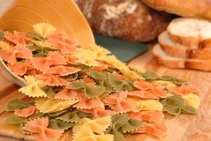 Farfalle pasta with bread. Uncooked tri-colored farfalle pasta spilling out of bowl onto cutting board with italian bread Stock Images