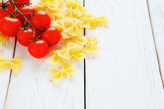 Farfalle pasta and cherry tomatoes Stock Images