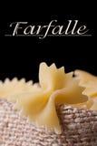 Farfalle pasta dry closeup on a black background Stock Photos