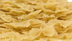 Pasta Farfalle Fill. Farfalle pasta falling on white background and filling the screen in slow motion stock video