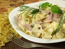 Farfalle pasta with ham Stock Photography