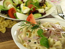 Farfalle pasta with ham on a plate Stock Photos