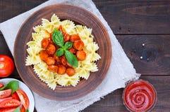 Farfalle pasta i en keramisk bunke, serve med ketchup, nya tomater, korv i tomatsås Royaltyfri Bild