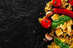 Farfalle pasta, peppar för röd chili, körsbärsröd tomat, basilika, svartpeppar, vitlök, parmesanost på mörk bakgrund Arkivbild
