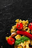 Farfalle pasta, peppar för röd chili, körsbärsröd tomat, basilika, svartpeppar, vitlök, parmesanost på mörk bakgrund Royaltyfri Foto