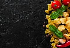 Farfalle pasta, peppar för röd chili, körsbärsröd tomat, basilika, svartpeppar, vitlök, parmesanost på mörk bakgrund Arkivbilder