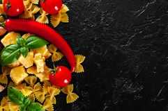 Farfalle pasta, red chili peppers, cherry tomato, basil, black pepper, garlic, parmesan cheese on dark background royalty free stock images