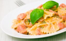 Farfalle pasta with sausage and cream sauce Stock Photo