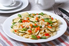Farfalle pasta with slices of vegetables, cheese closeup stock images