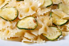Farfalle pasta with zucchini and cheese on a white plate macro Royalty Free Stock Photography
