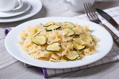 Farfalle pasta with zucchini and cheese on a white plate Royalty Free Stock Image