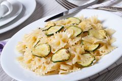 Farfalle pasta with zucchini slices closeup with a fork Royalty Free Stock Photography