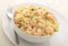 Farfalle with prawns. A bowl of farfalle with prawns in garlic butter, garnished with flat leaf parsley Stock Photo