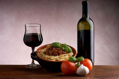 Farfalle with ragu sauce  and wine. Farfalle typical italian pasta with ragu sauce, basil and bottle of italian red wine Stock Image