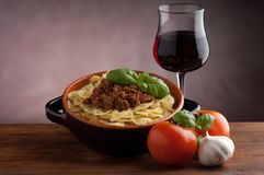 Farfalle with ragu sauce  and wine. Farfalle typical italian pasta with ragu sauce, basil and glass of italian red wine Royalty Free Stock Images