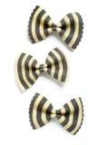Farfalle rayado blanco y negro o Bowtie Pasta en el fondo blanco Imagen de archivo libre de regalías