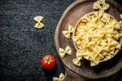 Farfalle surowy makaron w pucharze z pomidorem fotografia stock