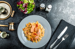 Farfalle with tomato sauce and roasted salmon Royalty Free Stock Photography