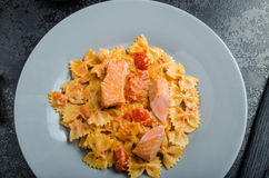 Farfalle with tomato sauce and roasted salmon Royalty Free Stock Image