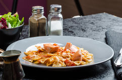 Farfalle with tomato sauce and roasted salmon Stock Images