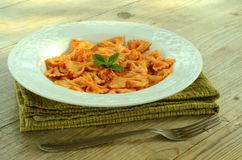 Farfalle with tomato and shrimps. Recipe of typical italian pasta, cooked with tomato sauce and shrimps, on table wood Stock Photos