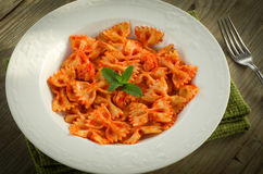 Farfalle with tomato and shrimps. Recipe of typical italian pasta, cooked with tomato sauce and shrimps, on table wood Stock Images