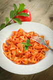 Farfalle with tomato and shrimps. Recipe of typical italian pasta, cooked with tomato sauce and shrimps, on table wood Royalty Free Stock Photos
