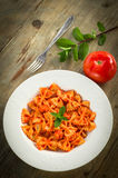 Farfalle with tomato and shrimps. Recipe of typical italian pasta, cooked with tomato sauce and shrimps, on table wood Royalty Free Stock Photography