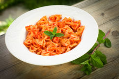 Farfalle with tomato and shrimps. Recipe of typical italian pasta, cooked with tomato sauce and shrimps, on table wood Royalty Free Stock Image