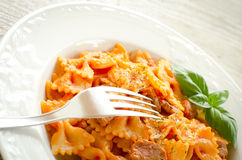 Farfalle topped with tomato sauce and meat Stock Images