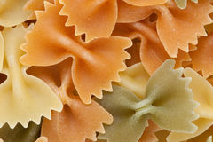 Farfalle  tricolore pasta background. Multicolored pasta with the addition of natural tomatoes and spinach Royalty Free Stock Photo