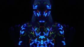 Farfalle ultraviolette di body art sul corpo di una ragazza che muove uniformemente il suo corpo video d archivio